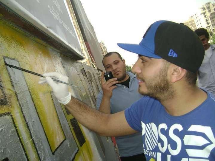 صور تامر حسني يكتب اسم شهداء التحرير على الجدار iqpic1c51cf36de.jpg